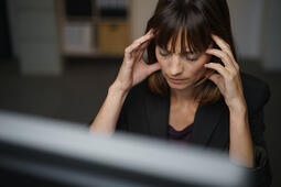 Businesswoman suffering from a headache or migraine holding her hands to her throbbing temples as she works late in the office to a deadline-1