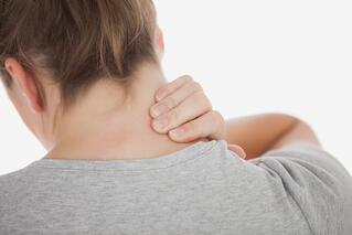 Close-up of woman suffering from neckache against white background.jpeg