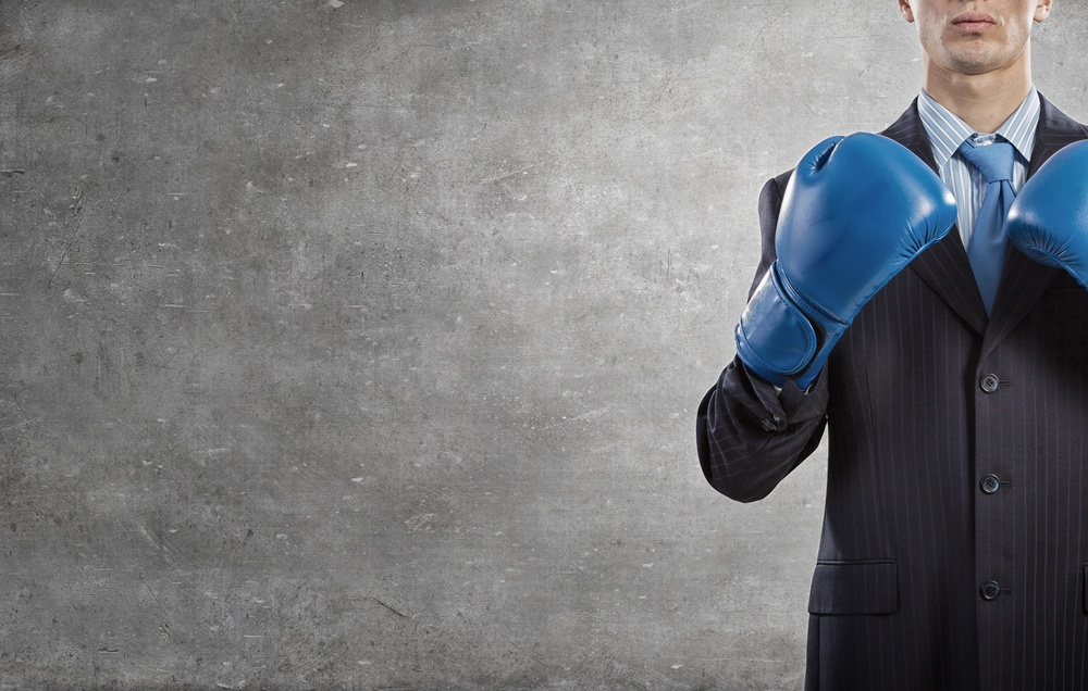Determined businessman in suit and boxing gloves.jpeg