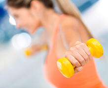 Woman at the gym lifting free weights